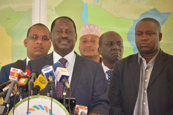 ODM Party Leader Raila Odinga addresses the media flanked by besieged Executive Director Magerer Lang'at (R) and other party officials.